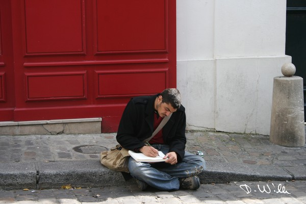 Art illustrator sitting on the street and drawing the scenery at Montmartre, Paris, France