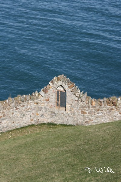 Window in a wall facing to the sea at Howth, Ireland
