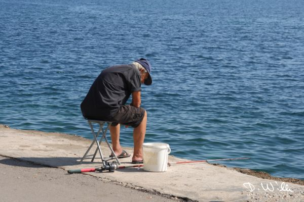 Old man fishing at the harbour of Chania, Crete, Greece