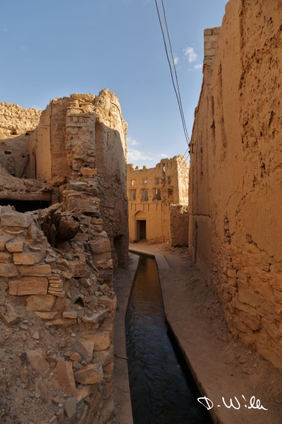 Water running through the ruins of an old loam town, Birkat al Mouz, Oman