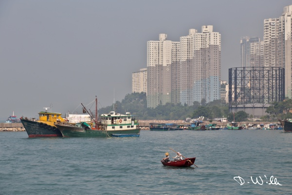 Small fishing boat at Aberdeen harbor with apartment blocks in the background, Aberdeen, Hong Kong